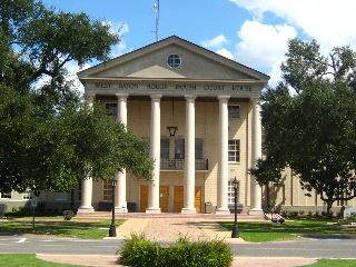 Large courthouse building surrounded by trees